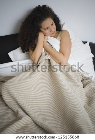 Woman in bed hugging blanket