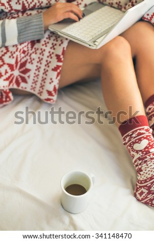 Woman in bed using lap top and drinking coffee - stock photo