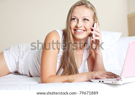 Woman in bed using the Internet and talking on the phone - stock photo