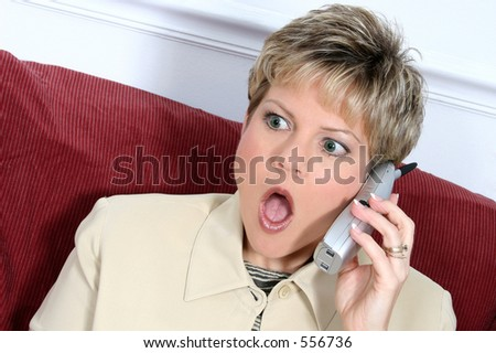 Woman in beige suit speaking on cordless phone.  Shocked expression. Blonde hair, green eyes.