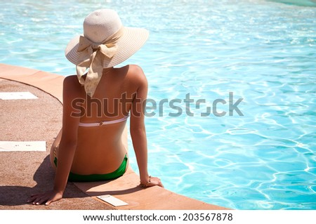 Woman in big hat relaxing on the swimming pool on sunny day. Girl relaxing at luxury travel resort.  - stock photo