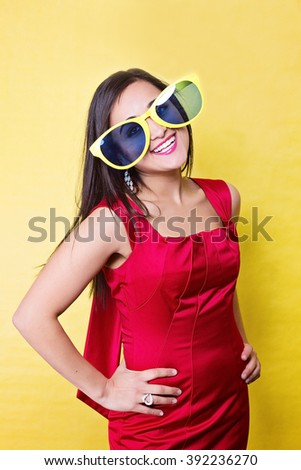 Woman in big sun glasses on yellow background