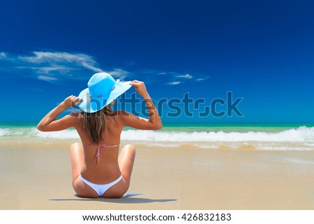 Woman in bikini and hat at tropical beach