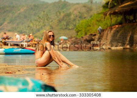 Woman in bikini and sunglasses posing on the beach with reflection near the boat - stock photo