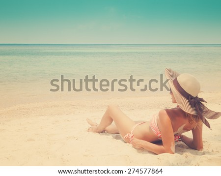 Woman in bikini at tropical beach, image with retro toning - stock photo