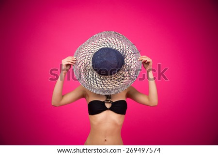 Woman in bikini covering her face with hat over pink background - stock photo