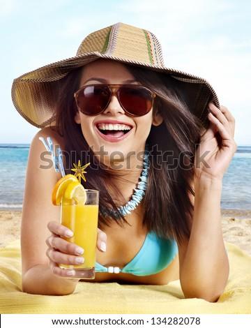 Woman in bikini drinking alcohol cocktail through a straw. - stock photo