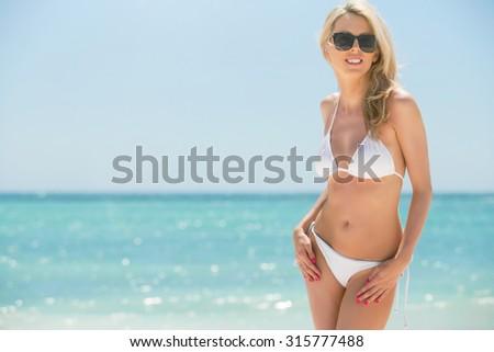 Woman in bikini enjoying summer on the beach - stock photo