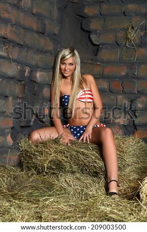 Woman in bikini on hay at wall - stock photo