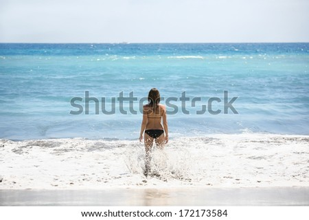 Woman in bikini standing at edge of ocean - stock photo