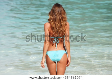 Woman in bikini standing on ocean beach on hot summer day - stock photo