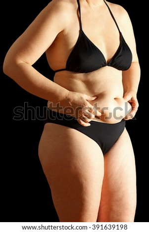 Woman in bikini with flabby stomach holding the excessive fat in her hands, black background - stock photo