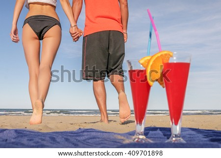 woman in bikini with man in beachwear on a sunny beach walking to the sea in summer on  honeymoon in a holiday destination with 2 cocktails lying on the sand