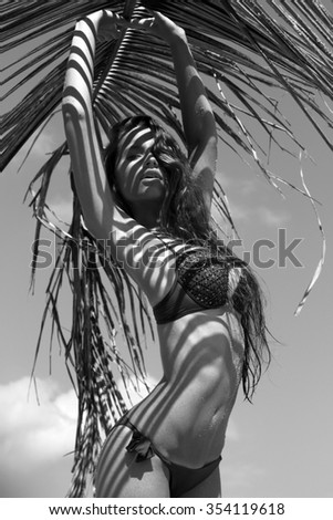 Woman in bikini with palm branch on beach near sea enjoying sun. Long wet hair. Volume curly hairstyle. Tropics. Hot summer day. Sexy girl. Vacation. Photo from Phuket island. Thailand