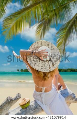 Woman in bikini with sunhat at tropical beach - stock photo