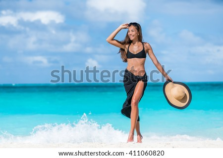 Woman in black bikini and sarong walking on beach. Elegant sexy girl wearing fashion beachwear putting on sunglasses and straw hat for sun uv protection enjoying her summer vacation in the Caribbean. - stock photo