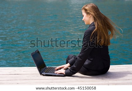 woman in black business suit sitting with laptop near the sea