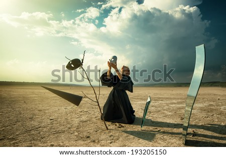 Woman in black cloak with a splinter of mirror in desert putting on her face a mask - stock photo