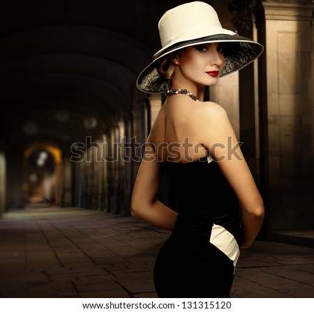 Woman in black dress and big white hat alone outdoors at night - stock photo
