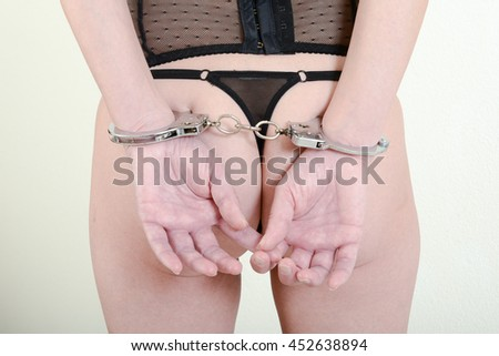 Woman in black dress and lingerie with handcuffs