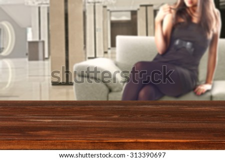 woman in black dress and sofa in room with red desk