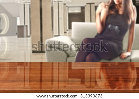 woman in black dress and sofa in room with wooden desk glasses top and sofa