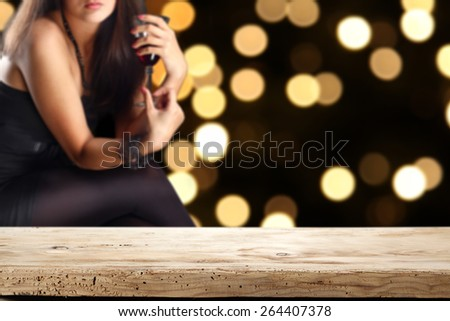 woman in black dress with glass of red wine and desk of wood and free space