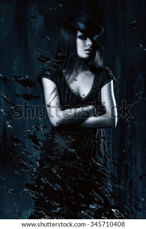 woman in black dress with hat and broken glass in dark room - stock photo