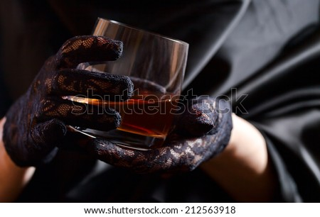 woman in black gloves with glass of whiskey - stock photo
