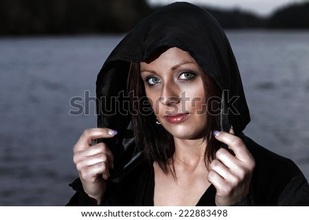 Woman in black hood out at night - stock photo