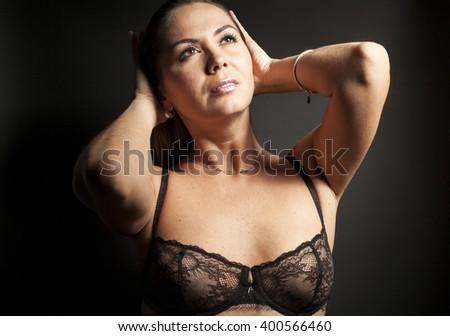 Woman in black lingerie on black background