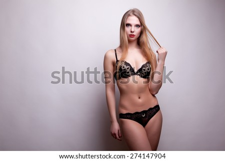 Woman in black linjerie on grey background. Studio shooting. Sensuality and beauty. - stock photo