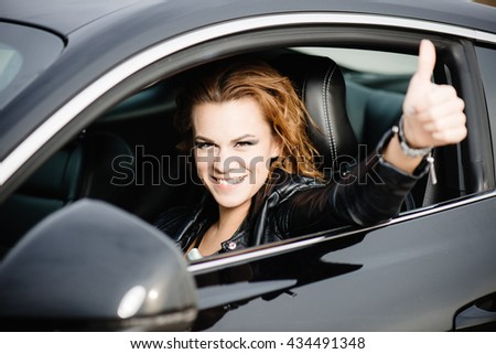 Woman in black sport car showing OK sign, thumb up   - stock photo