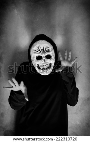 Woman in black with a plastic human skull mask - stock photo