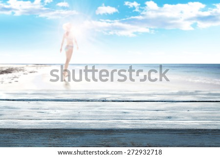woman in blue bikini on beach and wooden space