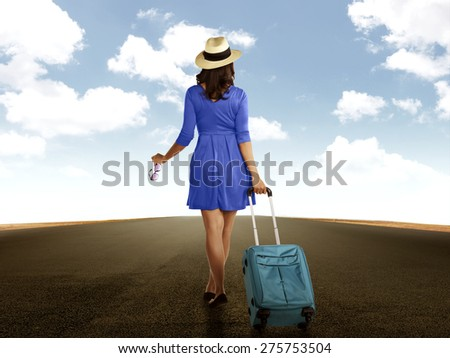 Woman in blue dress and hat, walking alone in empty road - stock photo