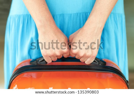 Woman in blue dress holds orange suitcase in hands.