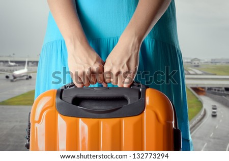 Woman in blue dress holds orange suitcase in hands on airport background.