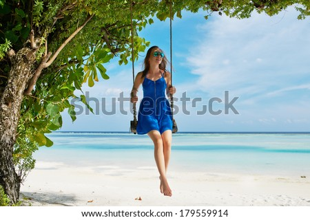 Woman in blue dress swinging at tropical beach - stock photo