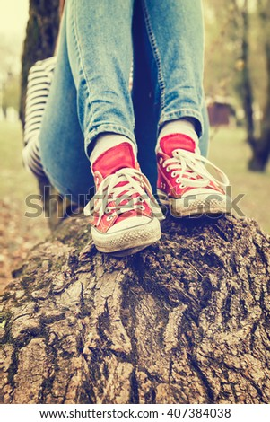Woman in blue jeans and red canvas sneakers sitting on a tree in a park. Retro styled photo. - stock photo