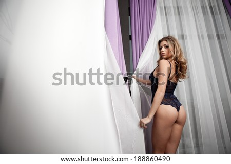 woman in blue lingerie standing near the window