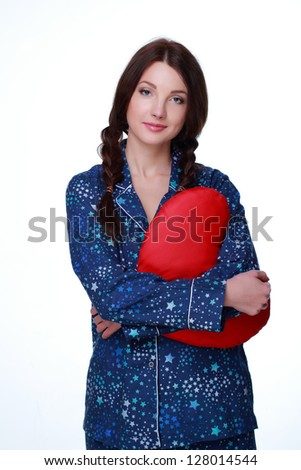 Woman in blue pajamas with heart-shaped pillow on white background on Holiday theme - stock photo