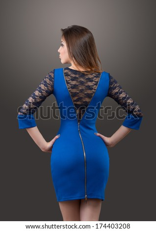 Woman in blue suit on gray background, view from back - stock photo