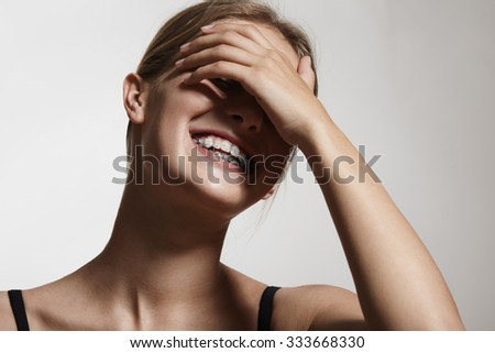 woman in braces is laughing and close her eyes with a hand - stock photo