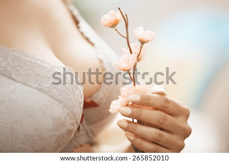 Woman in brassiere holding Sakura flower. Close-up horizontal photo