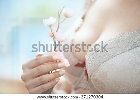 Woman in brassiere holding Sakura flower. Close-up horizontal photo - stock photo