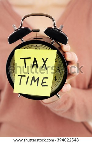 Woman in brown sweater holding alarm with tax time inscription, close up - stock photo