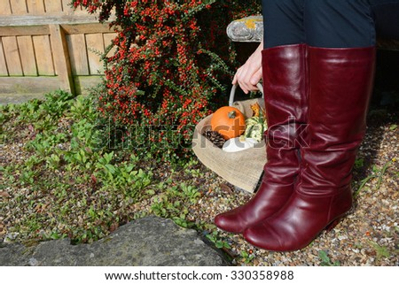 Woman in burgundy knee high boots sits on a bench, her hand resting on a basket of pumpkins - stock photo