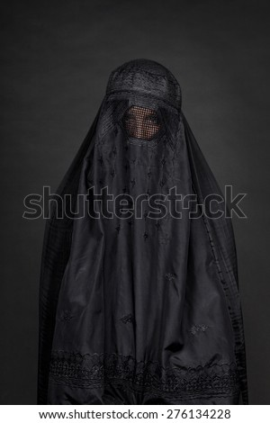 Woman in burka isolated on black medium