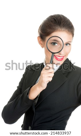 Woman in business dress looking through a magnifying glass. She is searching for something.